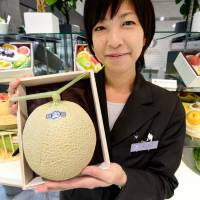 Bearing fruit: Miyuki Kaida, who works at the Sun Fruits luxury fruit store in Tokyo Midtown, shows a high-quality melon Sept. 17. | AFP-JIJI