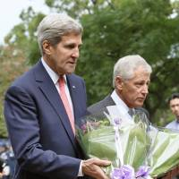 Pointed visit: U.S. Secretary of State John Kerry (left) and Defense Secretary Chuck Hagel lay flowers Thursday at Chidorigafuchi in Tokyo. | KYODO