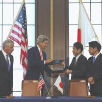 Swap shop: Signed documents are exchanged Thursday in Tokyo by (from left) U.S. Secretary of Defense Chuck Hagel, U.S. Secretary of State John Kerry, Foreign Minister Fumio Kishida and Defense Minister Itsunori Onodera. | POOL