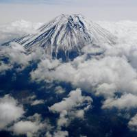 Mercury rising: The 3,776-meter peak of Mount Fuji is still mostly covered in snow in this aerial photo taken May 1. | KYODO