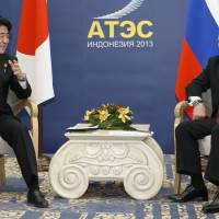 Forming trust: Prime Minister Shinzo Abe (left) and Russian President Vladimir Putin speak Monday in Indonesia. | KYODO