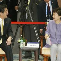 A start: Prime Minister Shinzo Abe and South Korean President Park Geun-hye chat Tuesday while attending the Asia-Pacific Economic Cooperation forum summit in Bali, Indonesia. | KYODO