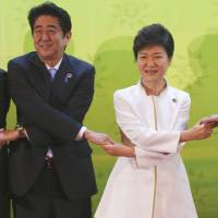 Common ground: Prime Minister Shinzo Abe (from left), South Korean President Park Geun-hye, Brunei Sultan Hassanal Bolkiah and Chinese Premier Li Keqiang join hands for a group photo at the Association of Southeast Asian Nations summit in Bandar Seri Begawan on Thursday. | AP