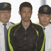 Nabbed: Charles Thomas Ikenaga, who has confessed to stalking and stabbing to death an 18-year-old female high school student, is escorted by police officers Thursday morning. | KYODO