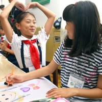 Giving peace a chance: An Inoue (right), a fifth-grader from Tokyo, draws a picture together with a 10-year-old girl in Pyongyang in late August. | KYODO