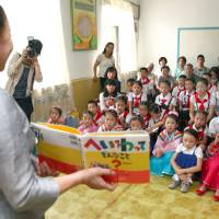 North Korean children at Rungra Elementary School listen to a teacher read a Japanese book. | KYODO