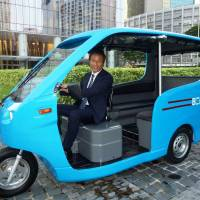 Electro-glide: Tokushi Nakashima, president of Uzushio Electric Co.'s subsidiary in the Philippines, rides the company's electric tricycle in Manila. | KYODO