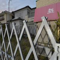 Worlds apart: A fence in Tomioka perches on the border of the no-go zone around the Fukushima No. 1 nuclear plant. | KYODO