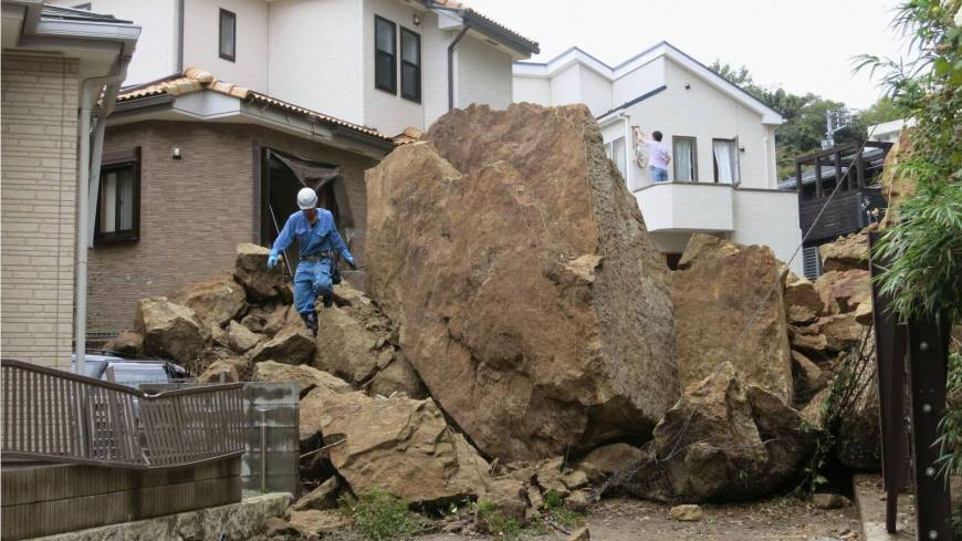 Crushing: A huge boulder lies in the road after ramming into a house in Kamakura, Kanagawa Prefecture, in a landslide caused by Typhoon Wipha on Wednesday. Right: Trees lie flattened on Izu-Oshima Island, south of Tokyo, the same day.