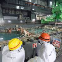 Danger zone: Fukushima Gov. Yuhei Sato (right) inspects the reactor 4 building Tuesday at the stricken Fukushima No. 1 nuclear plant, including the unit's spent-fuel pool (left). | KYODO