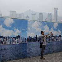 Don't breathe now: A man photographs himself in front of an image of Hong Kong's skyline on Aug. 22 as air pollution blanketed the city in a toxic haze. A WHO panel has designated outdoor air pollution as a leading cause of cancer in humans. | BLOOMBERG