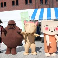 Having a fun time: Yasuyuki Morishita, the curator of Bizen Latin American Museum, stands with mascots Don Taino of the Dominican Republic, Peccary of Ecuador and I. Quimbaya of Colombia at the Yokohama Red Brick Warehouse on Sept. 28. | KYODO