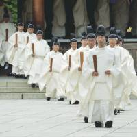 In step: Shinto priests exit Yasukuni's outer shrine Thursday after performing the Kiyoharai rite on the first day of the shrine's four-day autumn festival. | AFP-JIJI