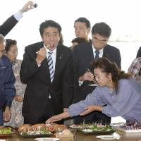 Stoical: Prime Minister Shinzo Abe (front, second from left) samples octopus and other marine produce caught off Fukushima Prefecture during a visit to the city of Soma on Saturday. | KYODO