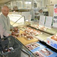 Test market: Consumers in a supermarket Sept. 26 in Soma, Fukushima, check out crab and other marine produce caught off the prefecture on a trial basis. | KYODO