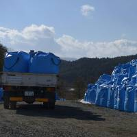 Behind schedule: A truck drops off plastic bags filled with radiation-tainted soil at a site in Kawauchi, Fukushima Prefecture, on March 5. | BLOOMBERG