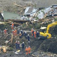 Never give up: Rescuers on Monday look for 18 people still missing on Oshima following mudslides triggered last week when  Typhoon Wipha dumped torrential rain on the island. Bad weather over the weekend forced the search to be suspended. | KYODO
