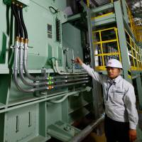 Energy source: An engineer at Toyota Motor East Japan, a car assembly subsidiary of Toyota Motor Corp., points to the company's gas engine cogeneration system at a plant in the small village of Ohira, Miyagi Prefecture, on Aug. 23. | AFP-JIJI