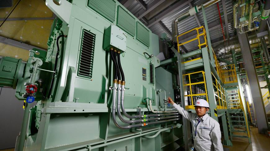 Energy source: An engineer at Toyota Motor East Japan, a car assembly subsidiary of Toyota Motor Corp., points to the company's gas engine cogeneration system at a plant in the small village of Ohira, Miyagi Prefecture, on Aug. 23.