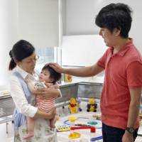 Focus on the family: A couple leaves their baby with staff members at a baby-sitting facility in the National Art Center in Tokyo in September before viewing the exhibits. | KYODO