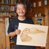 Burning desire: Pyrography artist Soji Hamada holds one of his favorite creations, a drawing of an owl, at his home in Shiojiri, Nagano Prefecture, on Sept. 4. | KYODO