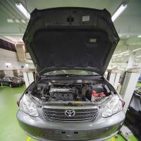 Up on the rack: A mechanic repairs a Toyota at a dealership in Singapore. A U.S. jury Friday ordered the automaker to pay $3 million in damages over the fatal crash of a defective Camry. | BLOOMBERG
