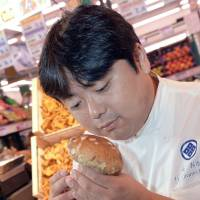 Undaunted: Harumoto Hagi, a chef from Fukushima Prefecture, sniffs mushrooms Monday during a visit to Paris. | AFP-JIJI