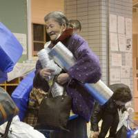 An elderly woman is relieved and leaves a shelter on Saturday evening after the evacuation order and advisory were lifted. | KYODO