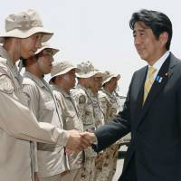 Security debate: Prime Minister Shinzo Abe meets Maritime Self-Defense Force personnel at their base in Djibouti, eastern Africa, in August. | KYODO