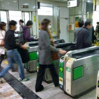 And they're off: Passengers pass through ticket gates at JR Shinjuku Station on Wednesday. | KYODO