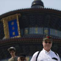 Just like heaven: A foreign tourist sporting a Communist Party hat visits the Temple of Heaven in Beijing in July.  | AP