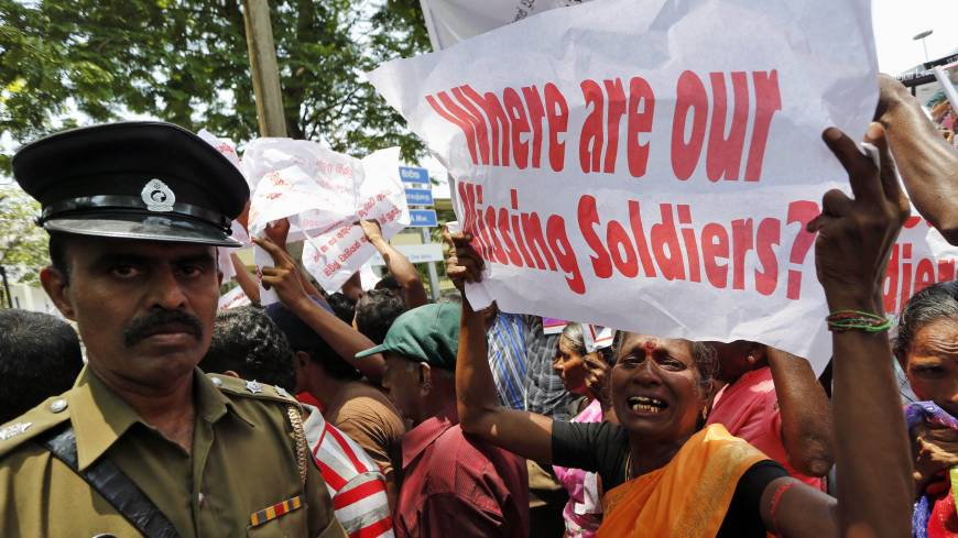 Questions persist: A Sri Lankan ethnic Tamil woman supporting the Dead and Missing Persons' Parents Front cries while holding a placard as a police officer watches during an August protest in Colombo