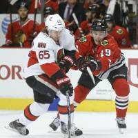 Forward thinking: Senators defenseman Erik Karlsson passes the puck past Blackhawks center Jonathan Toews in first-period action in Chicago on Tuesday. Chicago beat Ottawa 6-5 | AP