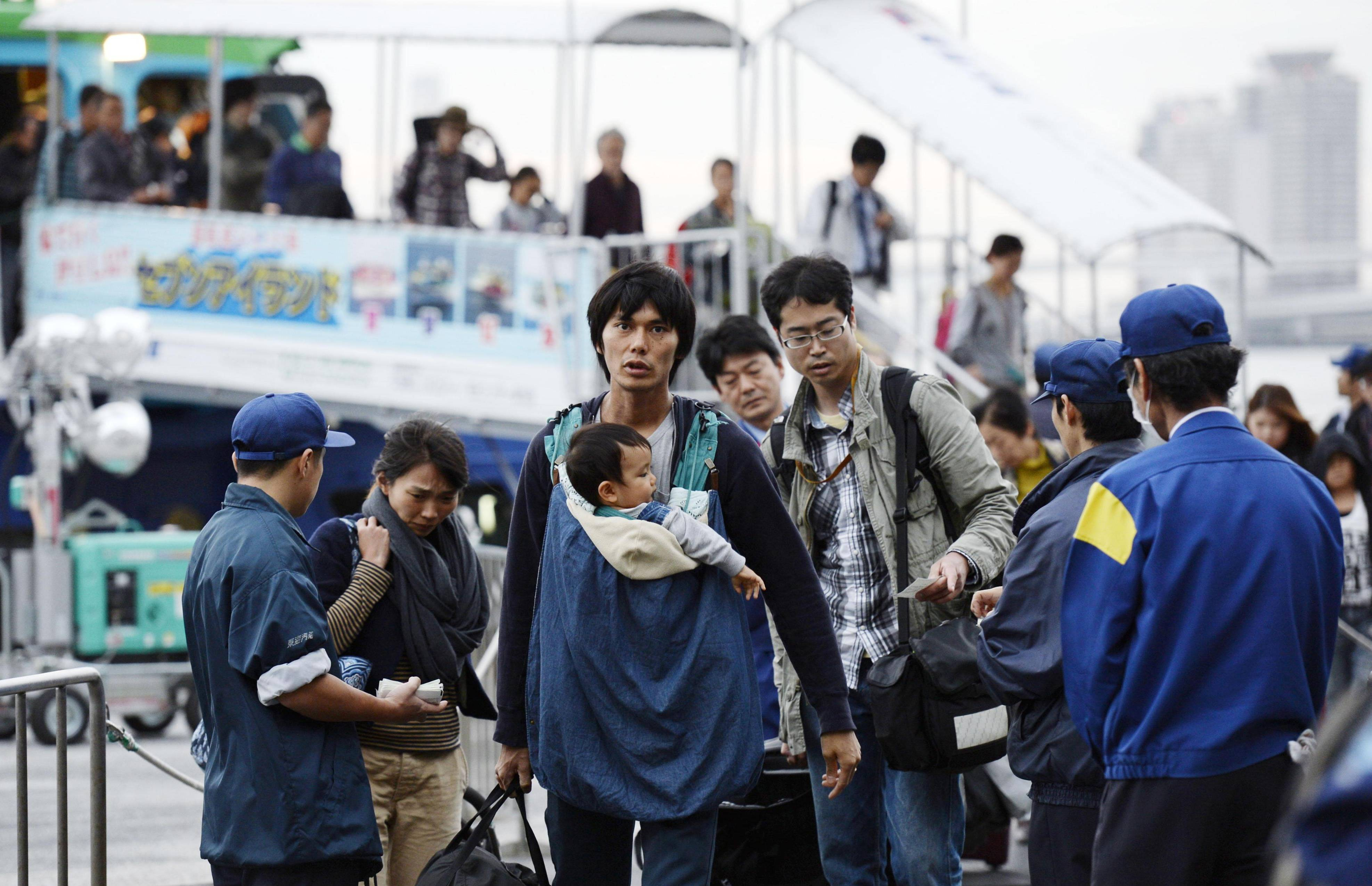 Out of harm's way: Residents of Izu-Oshima Island, who evacuated in the face of the second typhoon expected to hit the island in a little more than a week, arrive at the Takeshiba Passenger Ship Terminal in Tokyo on Tuesday.  | KYODO