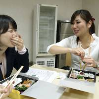 Brokerage employees eat 'bento' boxed lunches ordered using the Gochikuru food delivery website operated by Star Festival Inc.  | KYODO