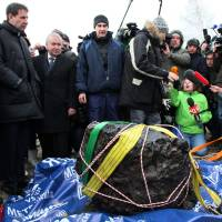 Meteoric: People gather around what scientists believe to be a chunk of the Chelyabinsk meteor, recovered from Chebarkul Lake, on Wednesday | AP