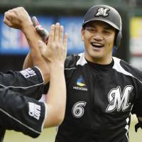 Stellar start: The Marines' Tadahito Iguchi is congratulated by teammates after hitting a first-inning solo home run in Game 1 of the Pacific League Climax Series First Stage on Saturday at Seibu Dome. Iguchi went 2-for-4 with three RBIs. | KYODO