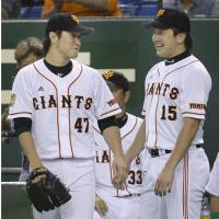 Dynamic duo: Giants relievers Tetsuya Yamaguchi (left) and Hirokazu Sawamura helped keep the Carp offense in check in the latter stages of Game 1 on Wednesday. | KYODO