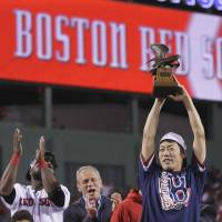 Best of the best: Red Sox closer Koji Uehara lifts the American League Championship Series MVP trophy after Boston advanced to the World Series with a 5-2 win over the Tigers on Saturday night at Fenway Park. | AP
