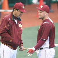 All wet: Eagles manager Senichi Hoshino speaks with Casey McGehee during practice on Sunday. | KYODO