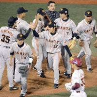 Strictly business: Yomiuri Giants players celebrate their Game 1 victory on Saturday at Kleenex Stadium. | KYODO