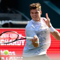 On a roll: Canada's Milos Raonic plays a shot from France's Jeremy Chardy in their second-round match at the Rakuten Japan Open on Thursday at Ariake Colosseum. Raonic won 6-4, 6-3. | AFP-JIJI