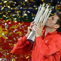Sealed with a kiss: Novak Djokovic lifts the winner's trophy after beating Juan Martin del Potro in the final of the Shanghai Rolex Masters on Sunday night. | AFP-JIJI