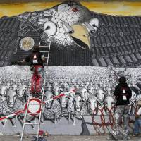 Eagle-eyed: Artists from the group Captain Borderline paint a mural called 'Surveillance of the Fittest' on a wall in Cologne, Germany, on Thursday. The painting, which they hope will draw attention to the U.S. National Security Agency's spy program, depicts an American bald eagle with surveillance cameras watching a herd of sheep | AP