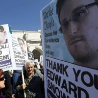 Up in arms: Demonstrators hold up banners with photos of Edward Snowden during a protest outside of the U.S. Capitol in Washington on Saturday. Protesters demanded that Congress investigate the National Security Agency's mass surveillance programs | AP