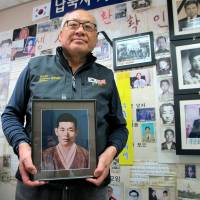 Rogue rescuer: Choi Sung-yong, an activist who is fighting for the return of South Koreans kidnapped by the North, holds a photo of his father, Choi Won-mo, one of the kidnapping victims, at his Seoul office on Oct. 21. Although some have called him a lifesaver, not everyone likes the way he operates | THE WASHINGTON POST