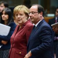 German Chancellor Angela Merkel and French President Francois Hollande arrive at the European Council meeting at the EU headquarters in Brussels on Thursday | AFP-JIJI