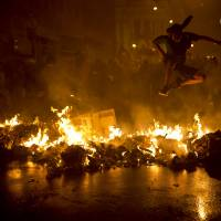 Black Blocked: A Black Bloc anarchist jumps over a burning barricade at Cinelandia Square during a march in support of teachers on strike in Rio de Janeiro on Oct. 7. The Black Bloc, a violent form of protest and vandalism that emerged in the 1980s in West Germany, has become a driving force behind demonstrations in Brazil in recent weeks. Young Brazilians are following the anti-capitalist tenets of earlier versions, smashing scores of banks and multinational businesses and directly confronting riot police | AP