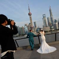 Till divorce do us part: A Chinese couple pose for wedding photos on the Bund in Shanghai on Tuesday. Divorce rates in China's two wealthiest cities, Beijing and Shanghai, have soared after the announcement of a property tax that includes a loophole for couples who split up. Nearly 40,000 couples divorced in Beijing in the first nine months of this year, up 41 percent from the same period in 2012 | AFP-JIJI