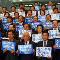 Sending a message: Opposition lawmakers stage a protest Tuesday at the National Assembly in Seoul to accuse the government of covering up meddling by the country's spy agency in last December's presidential poll. The banners read: 'Stop covering up' and 'Stop putting pressure on investigators.'  | AFP-JIJI